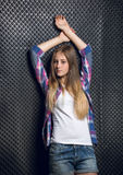 Blonde girl in checkered shirt leaning against black wall Royalty Free Stock Photos