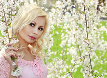 Blonde Girl with Cherry Blossom. Spring Portrait. stock photo