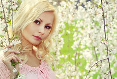 Blonde Girl with Cherry Blossom. Spring Portrait Stock Photos