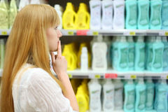 Blonde girl chooses abstergent in shop. Shallow depth of field Stock Photo