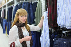 Blonde girl chooses male shirt in shop Stock Photos
