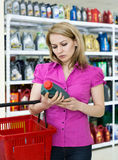 Blonde girl chooses motor oil in auto parts store. Consults by phone Royalty Free Stock Image