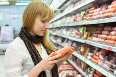 Blonde girl chooses sausage in store Stock Photos