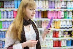 Blonde girl chooses shampoo in large store Stock Photos