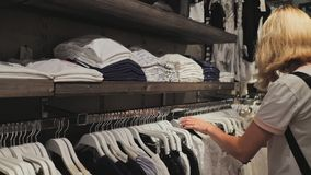 Blonde girl chooses things in the women`s clothing store. stock video