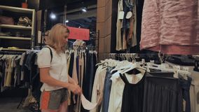Blonde girl chooses things in the women`s clothing store. stock footage