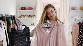Blonde girl choosing black and beige blouse on hangers comparing them in front of a mirror deciding what to buy. Smiling. Cheerful girl in clothes boutique stock footage