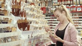 Female artist in art store. Blonde girl choosing new brushes in a art department store, creative artist buying art tools. Wide choice of different brushes stock video