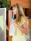 Blonde girl cleaning glass door of furniture Royalty Free Stock Photos