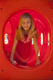 Blonde Girl Climbing Through Glowing Tube at Park Royalty Free Stock Image