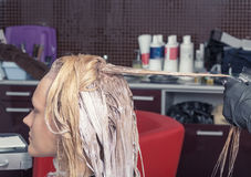 A blonde girl coloring hair Royalty Free Stock Images