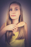 Blonde girl combing her hair, grain effect Royalty Free Stock Images