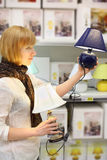 Blonde girl compares two table lamps in shop Royalty Free Stock Images