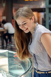 Blonde girl considers jewelry in the store. Young woman looking at the shop showcase and taking jewelry to look at it closer. Blonde girl considers jewelry in stock images