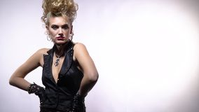 Blonde girl with crazy hairstyle wearing black vest, posing in the studio. Beautiful young blonde woman in rocker clothes, with her arms on the sides, posing in stock footage
