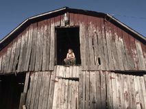 Blonde girl crouching in hay loft doorway with eyes closed. Young blonde girl in camouflage pants and green tank top crouching in hay loft doorway with eyes royalty free stock images