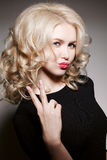 Blonde girl with curly hair seductive posing at camera, gesturing peace sign by fingers and making duck face. Woman sending blowin Royalty Free Stock Image