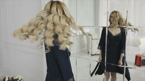 Blonde girl with curly hair turning around herself in front of the mirror in the morning. Studio shot. Slow motion 120fps stock video footage