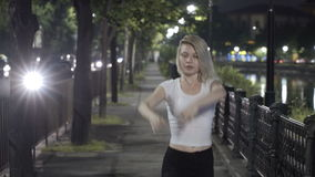Blonde girl dancing ballet on street at night expressing grace and elegance stock video footage