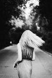 Blonde girl dancing on the road. Black and white. Stock Image