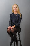 Blonde girl in dark outfit, sitting on a bar stool Royalty Free Stock Photos