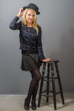 Blonde girl in dark outfit, standing near bar stool with a hat Royalty Free Stock Photo