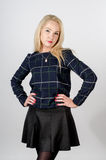 Blonde girl in dark outfit, uncertain look Royalty Free Stock Image