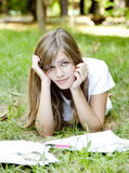 Blonde girl doing homework at the park. Stock Photos
