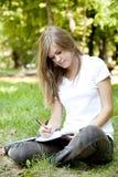 Blonde girl doing homework at the park. Stock Photo