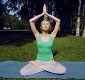Blonde girl doing yoga in park Stock Photo