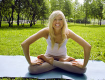 Blonde girl doing yoga in park Stock Photography