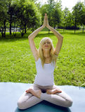 Blonde girl doing yoga in park Royalty Free Stock Photography