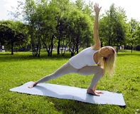 Blonde girl doing yoga in park Stock Image