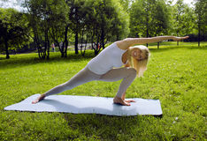 Blonde girl doing yoga in park Stock Photos