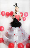 The blonde girl dressed as a playboy Bunny for Valentine's day. With hearts in his hands Royalty Free Stock Images