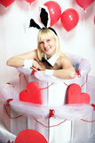 The blonde girl dressed as a playboy Bunny for Valentine's day. With hearts in his hands Royalty Free Stock Image