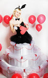 The blonde girl dressed as a playboy Bunny for Valentine's day. With hearts in his hands Stock Photos