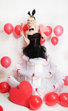 The blonde girl dressed as a playboy Bunny for Valentine's day. With hearts in his hands Royalty Free Stock Photography