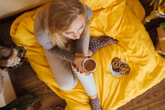 Blonde girl drinking her coffee, eat cookies and read a book Stock Photo