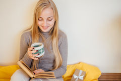 Blonde girl drinking her coffee, eat cookies and read a book Royalty Free Stock Images