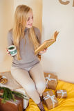 Blonde girl drinking her coffee, eat cookies and read a book Royalty Free Stock Image