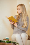 Blonde girl drinking her coffee, eat cookies and read a book Stock Image