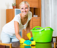 Blonde girl dusting in living room. Cheerful girl in rubber gloves dusting furniture in living room and smiling royalty free stock photo