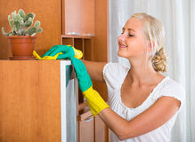 Blonde girl dusting in living room. Cheerful blonde woman in rubber gloves dusting furniture at home and smiling stock photos