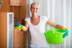 Blonde girl dusting in living room. Happy blonde girl in rubber gloves dusting furniture and smiling stock photo