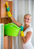 Blonde girl dusting in living room. Blonde girl in rubber gloves dusting furniture and smiling royalty free stock images