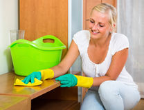 Blonde girl dusting in living room. Smiling young housewife in rubber gloves dusting furniture in living room royalty free stock photo