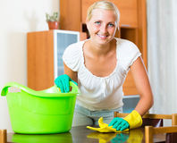 Blonde girl dusting in living room. Smiling young blonde in rubber gloves dusting furniture in living room royalty free stock images