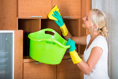 Blonde girl dusting in living room. Smiling young woman in rubber gloves dusting furniture in living room stock image