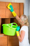Blonde girl dusting in living room. Young woman in rubber gloves dusting furniture at home and smiling royalty free stock photos